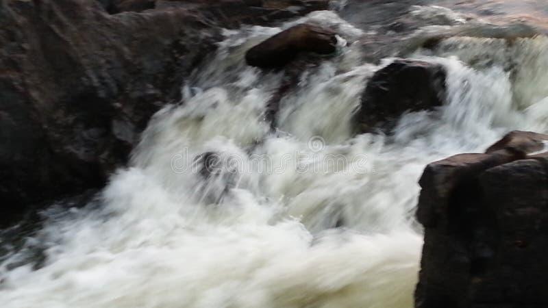 Écoulements d'eau blancs laiteux surmontant tout l'it& x27 ; défis de s image libre de droits