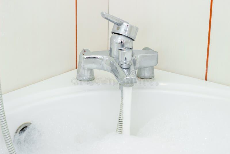 Écoulements d'eau dans la salle de bains d'un robinet ouvert images libres de droits