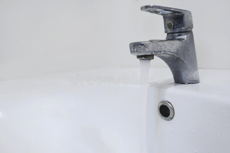 Écoulements d'eau de plan rapproché du robinet dans la salle de bains photos stock