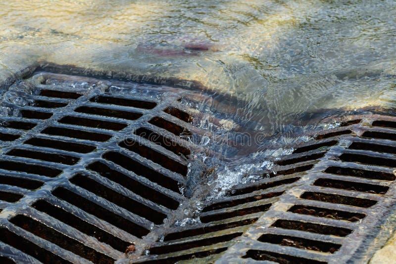 Écoulements d'eau fondus vers le bas par le trou d'homme image stock