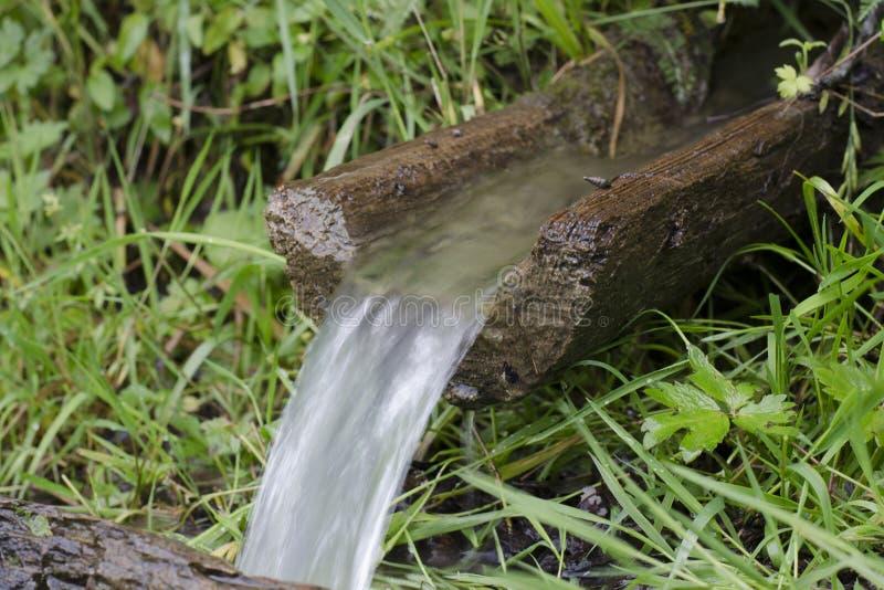 Écoulements d'eau par un descendeur en bois images stock
