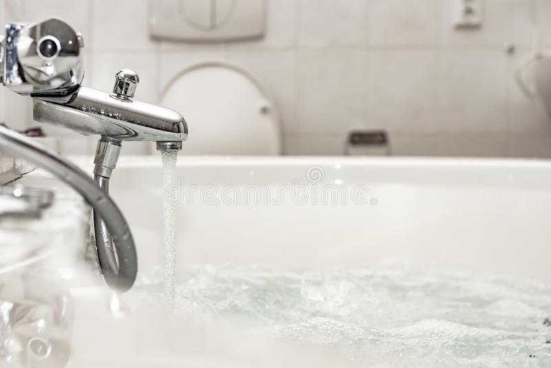 Écoulements d'eau d'un mélangeur de chrome à un bain ou à un tourbillon luxueux de station thermale, avec des bulles d'air à déte photos libres de droits