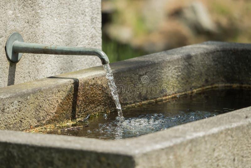 Écoulements d'eau d'un robinet à la fontaine en pierre photos libres de droits
