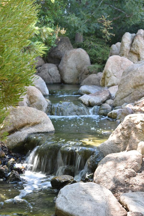 Écoulements de courant de cascade paisibles par les roches photos libres de droits