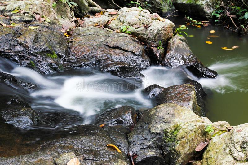 Écoulements de l'eau et roches laiteux de cascade photographie stock