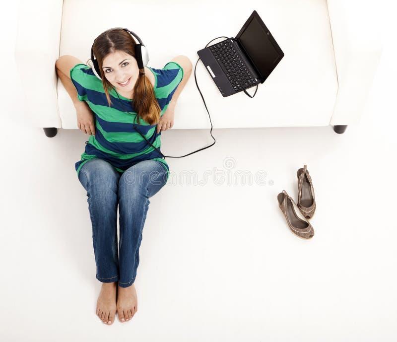 Écoutent la musique sur un ordinateur portatif photographie stock
