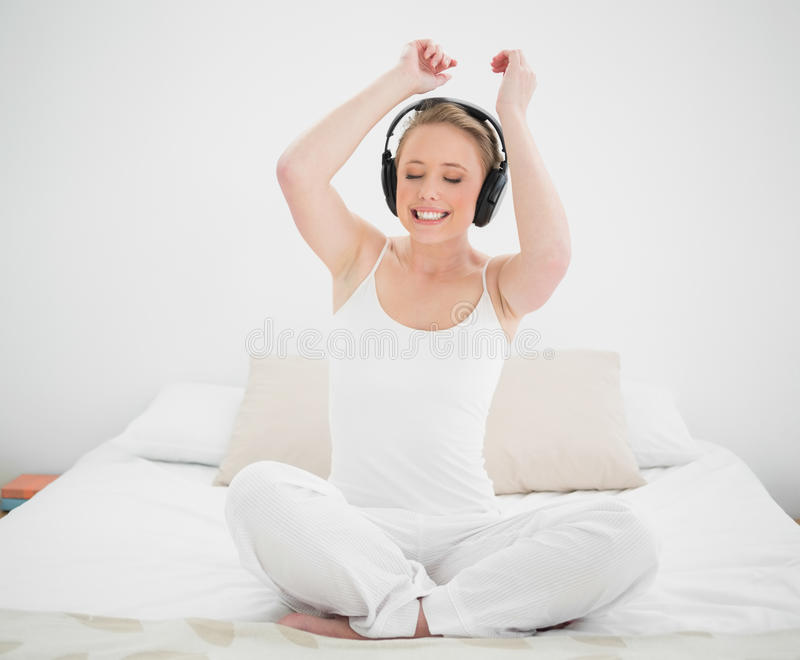 Écouter blond gai naturel la musique et bras dans le ciel images stock