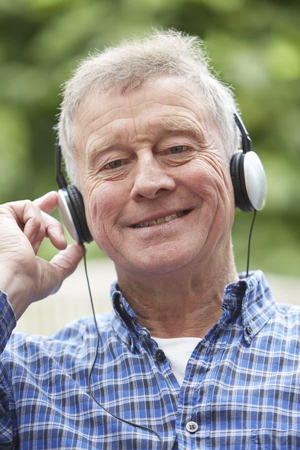 Écouter de détente d'homme supérieur la musique sur des écouteurs photo libre de droits