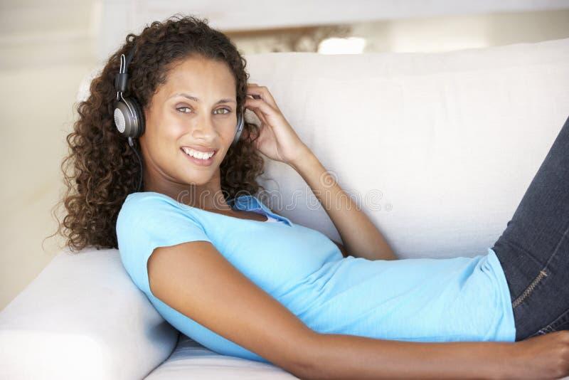 Écouter de détente de jeune femme la musique à la maison images stock