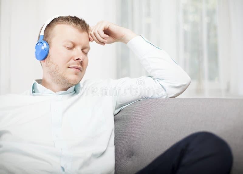 Écouter de détente de jeune homme la musique image stock