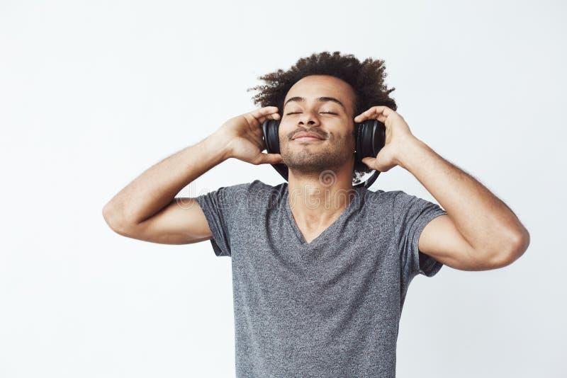Écouter de sourire d'homme africain heureux la musique dans des écouteurs Yeux fermés images libres de droits