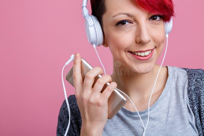 Écouter de sourire de fille heureuse la musique gentille sur des écouteurs photos libres de droits