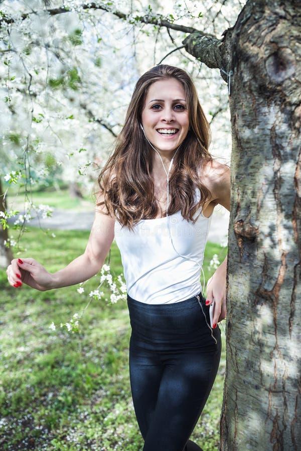 ?couter de sourire de jeune femme la musique ou podcast par l'interm?diaire des ?couteurs sous les arbres de floraison photo libre de droits