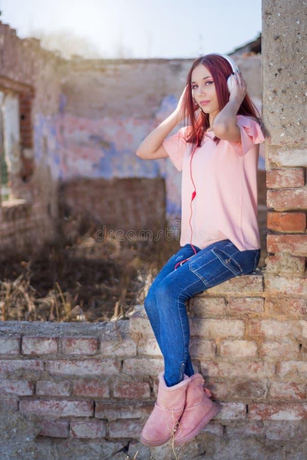 Écouter femelle de Redheads la musique sur des écouteurs sur des ruines murent les briques rouges de la rétro maison dans le couc photos libres de droits