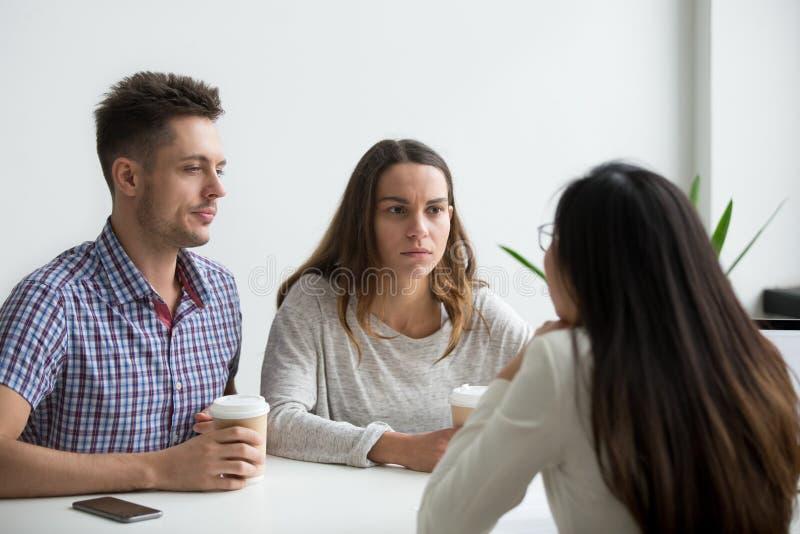 Écouter méfiant de couples méfiants douteux le businesswoma photo libre de droits