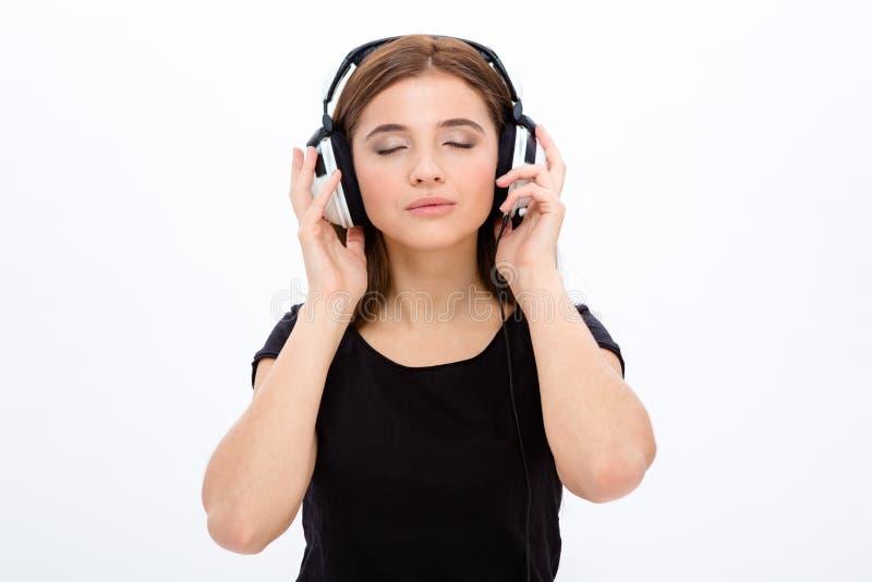Écouter woan assez jeune serein décontracté le musi utilisant des écouteurs photographie stock libre de droits