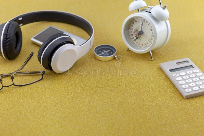 Écouteur avec le réveil, la boussole et la calculatrice blancs sur le fond de papier brillant de scintillement de texture de scin photos stock