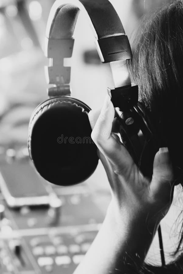 Écouteur de participation de femme sur l'oreille pour le soundcheck dans un studio photographie stock