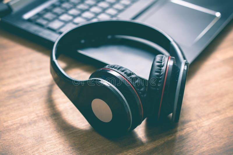 Écouteurs aériens sans fil noirs se trouvant sur le coin d'un clavier d'ordinateur portable dans un bureau photos stock