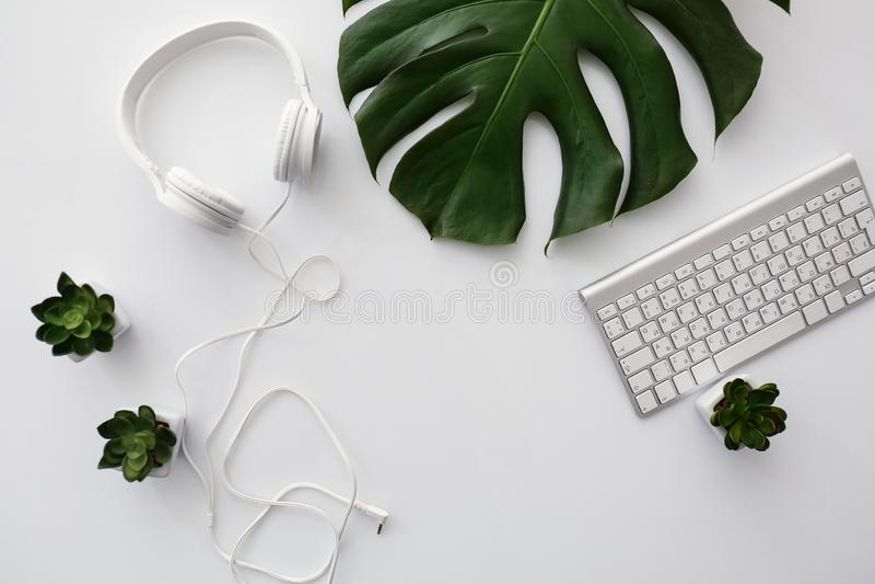 Écouteurs avec le clavier d'ordinateur et la feuille tropicale sur la table blanche images libres de droits