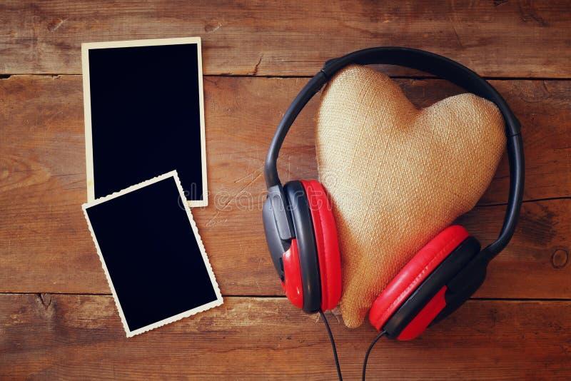 Écouteurs avec le coeur de tissu à côté des cadres vides de photo images libres de droits