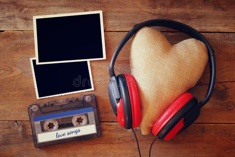 Écouteurs avec le coeur de tissu à côté des cadres vides de photo photographie stock libre de droits