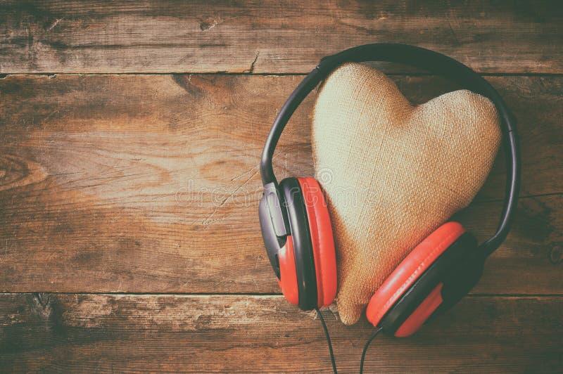 écouteurs avec le coeur de tissu au-dessus du fond en bois image libre de droits
