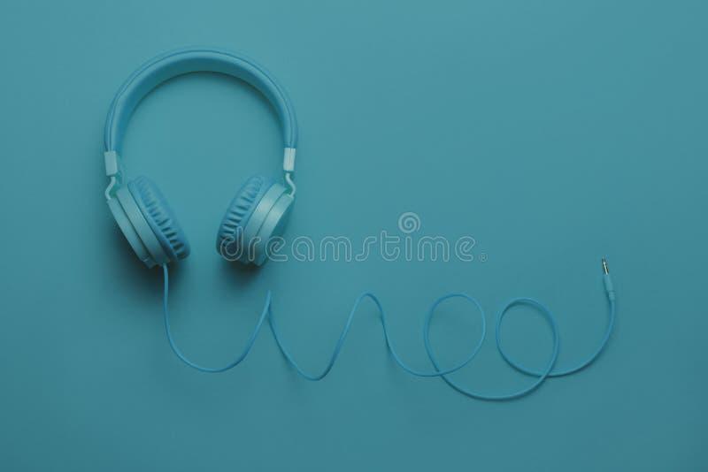 Écouteurs bleus sur le fond bleu Concept de musique photos stock