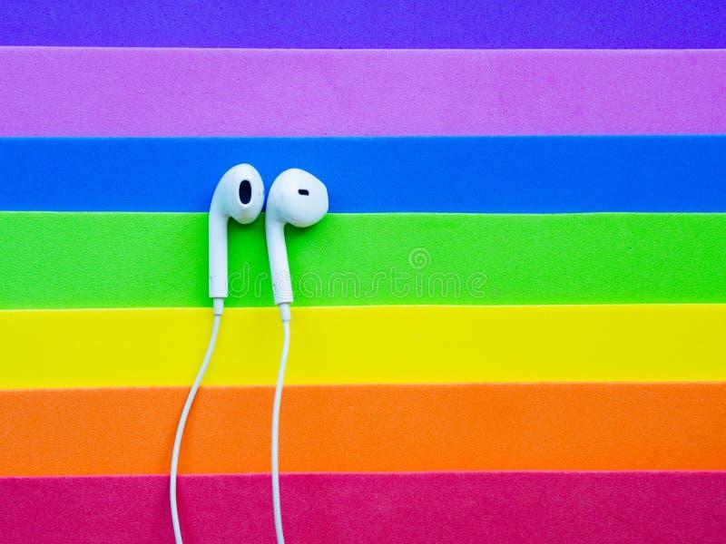 Écouteurs de câble blancs, casque sur un lgbt multicolore de fond d'arc-en-ciel photo libre de droits