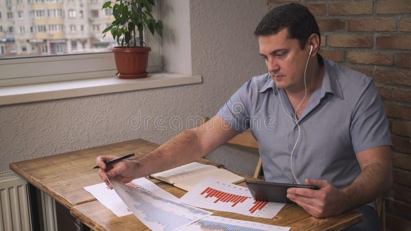 Écouteurs de directeur parlant en ligne avec un comprimé, diagrammes changeants de ventes sur la table Lieu de travail dans un bu image stock