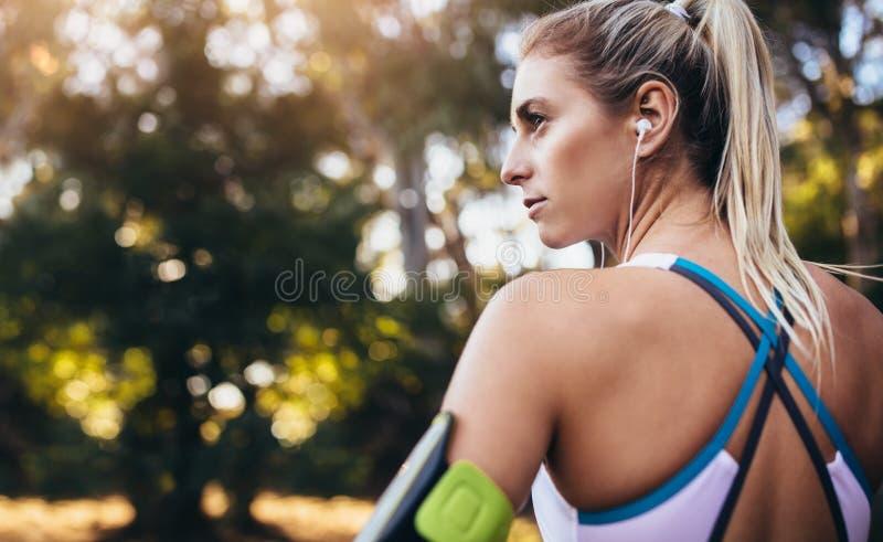 Écouteurs de port de coureur de femme pendant la séance d'entraînement photographie stock libre de droits