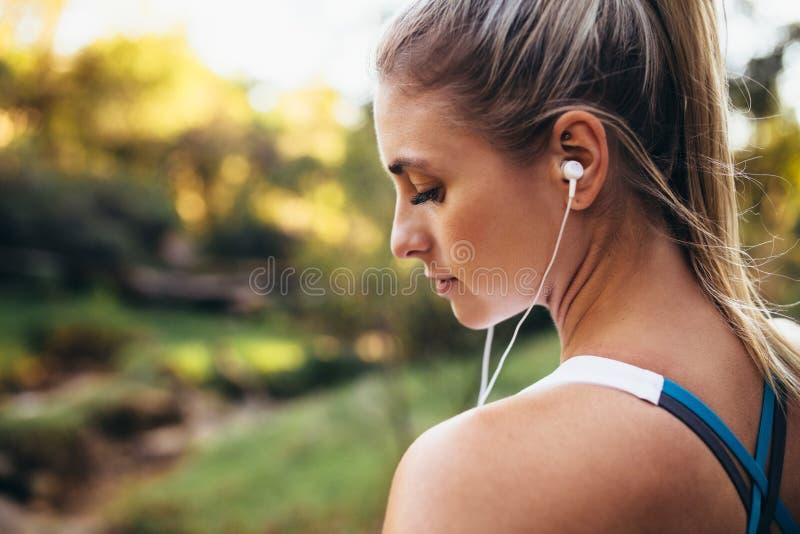Écouteurs de port de coureur de femme pendant la séance d'entraînement image stock