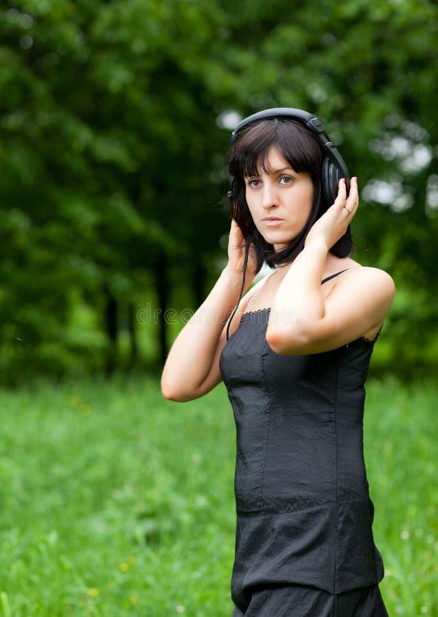Écouteurs de port d'une jeune femme photo libre de droits