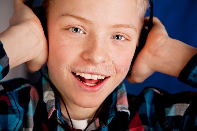 Écouteurs de port de jeune adolescent heureux images stock