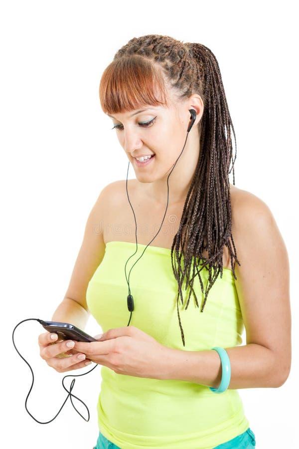 Écouteurs de port de jeune femme écoutant la musique au-dessus du phone futé images stock