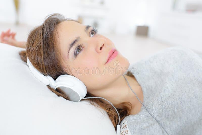 Écouteurs de port de femme sereine photos stock