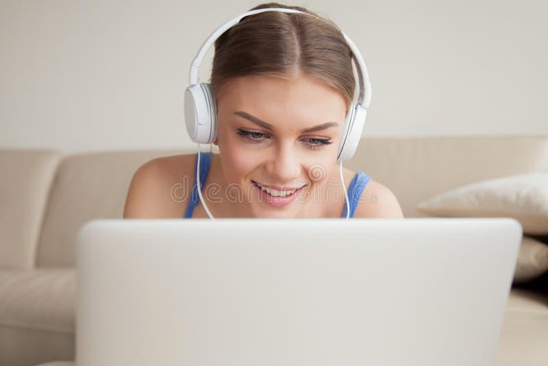 Écouteurs de port de sourire de jeune femme utilisant l'ordinateur portable, headshot image libre de droits