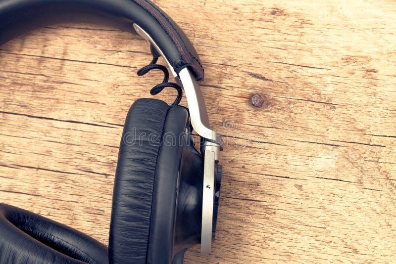 Écouteurs de vintage sur la table en bois - rétro concept de musique Image filtrée : effet de vintage traité par croix image stock