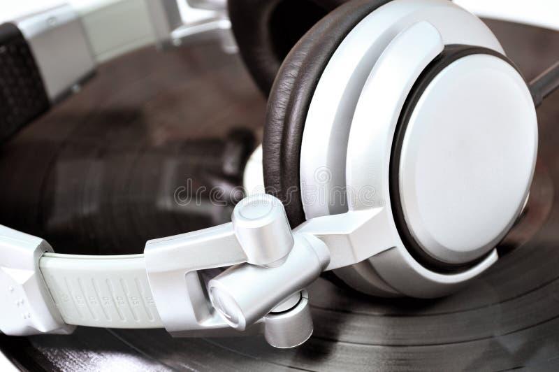 Écouteurs du DJ se trouvant au-dessus du vinyle noir photo stock