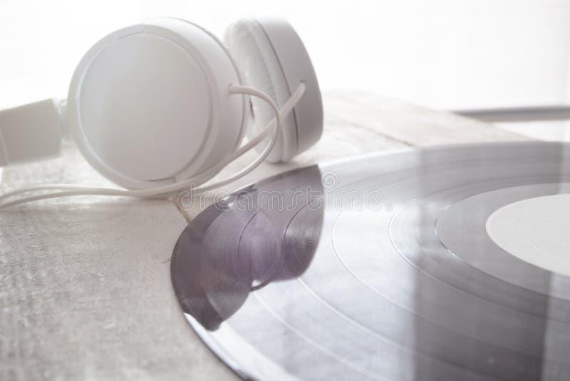 Écouteurs et disque de vinyle sur une table en bois blanche photos stock