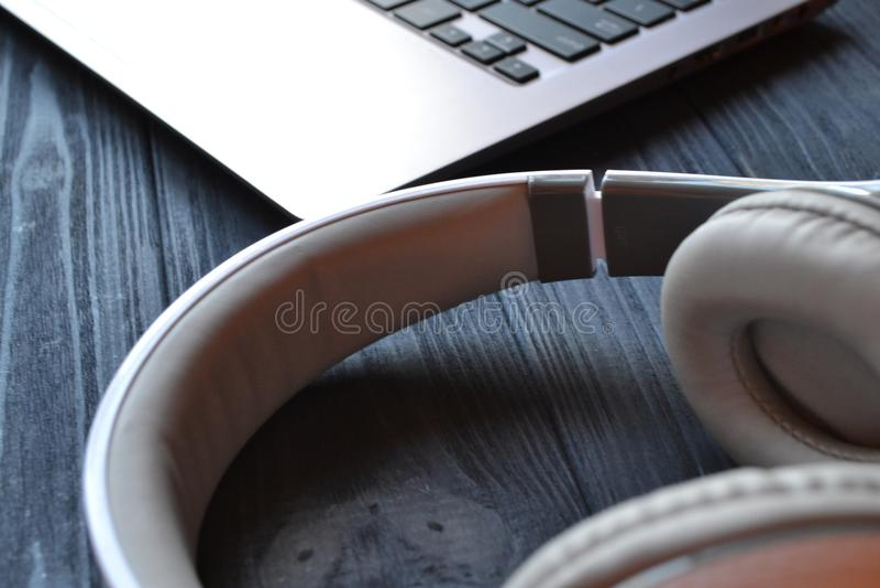 Écouteurs et ordinateur portable sur le bureau en bois bleu-foncé photographie stock libre de droits