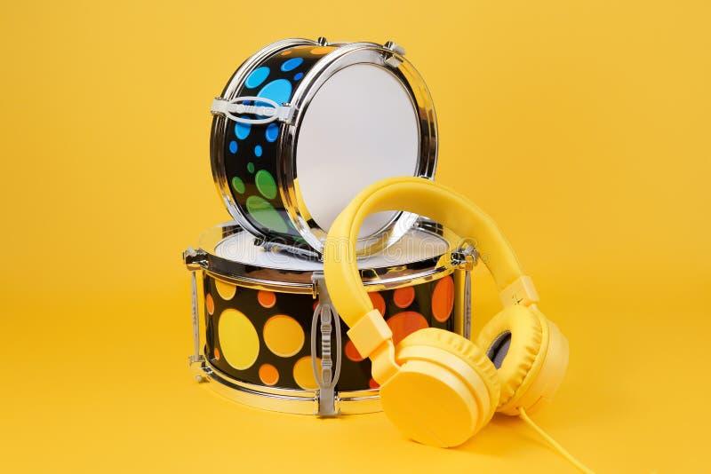 Écouteurs jaunes et mini kit de tambour sur le fond jaune Tambours de jouet image libre de droits