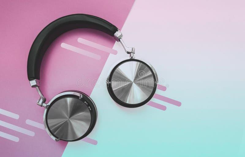 Écouteurs noirs de mode sur le fond rose de gradient Heure d'?t? urbaine image stock