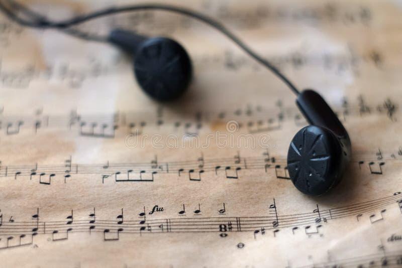 Écouteurs noirs sur la vieille musique de feuille image stock