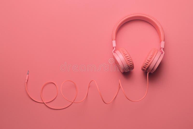 Écouteurs roses sur le fond rose Concept de musique images libres de droits