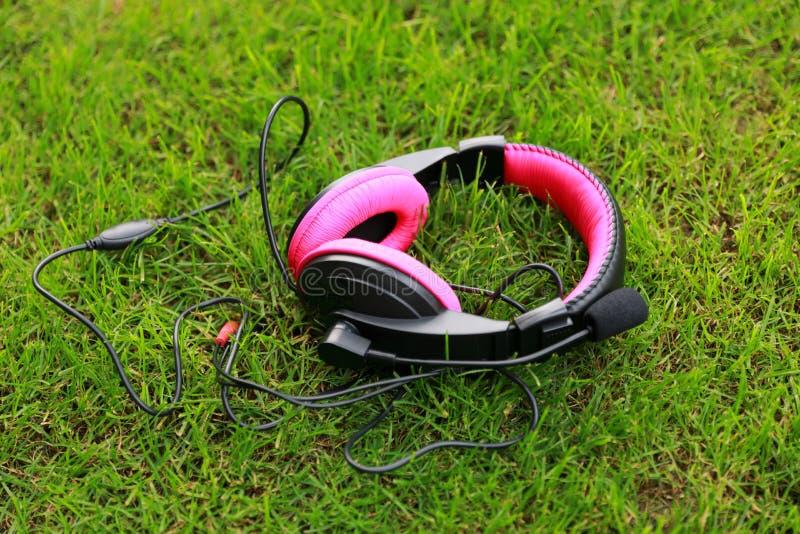 Écouteurs rouges noirs sur l'herbe verte Dispositif, musique photographie stock libre de droits
