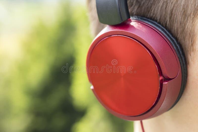 Écouteurs rouges sur la tête d'un adolescent images stock