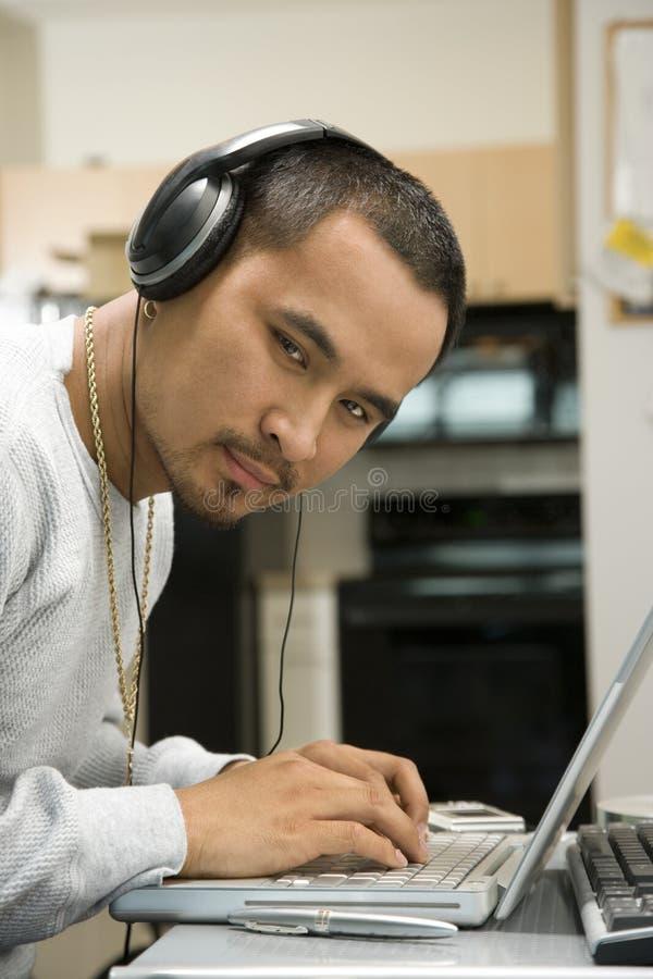 Écouteurs s'usants d'homme regardant le visualisateur. photo stock