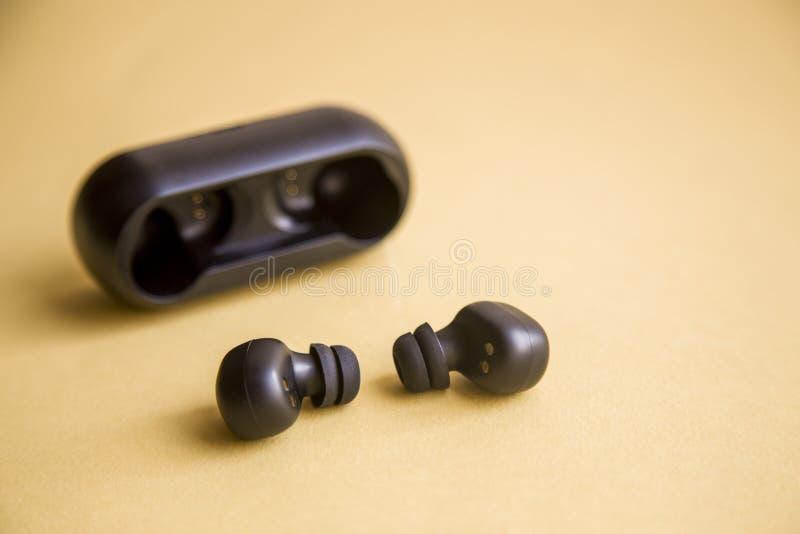 Écouteurs sans fil noirs avec le microphone sur le fond jaune photo stock