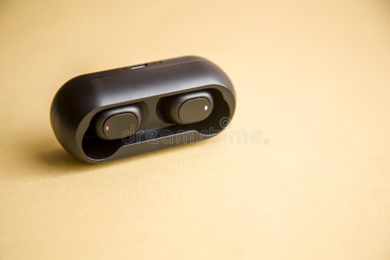 Écouteurs sans fil noirs avec le microphone sur le fond jaune photos stock